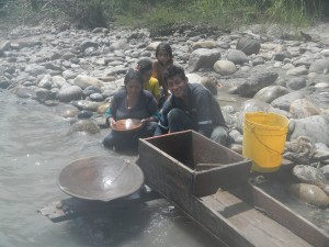 A family of artisanal miners pans for gold on the banks of the Río Jatunyacu.