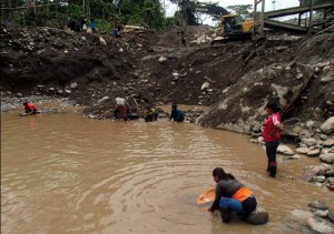 Community members panning for gold under precarious conditions.